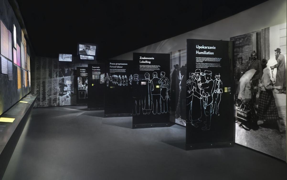 Warsztaty edukacyjne dla szkół ponadpodstawowych. Na zdjęciu galeria Zagłada - pomieszczenie z czarnymi ścianami działowymi, na których białymi literami przedstawione są informacje o formach prześladowania, którymi posługiwali się naziści w stosunku do Żydów w czasie II wojny światowej