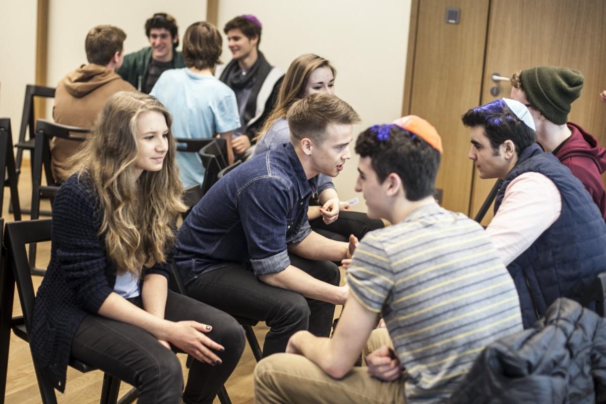 Warsztaty edukacyjne dla szkół ponadpodstawowych. Na zdjęciu: grupa młodych ludzi siedzi na krzesłach naprzeciwko siebie. Dyskutują ze sobą.
