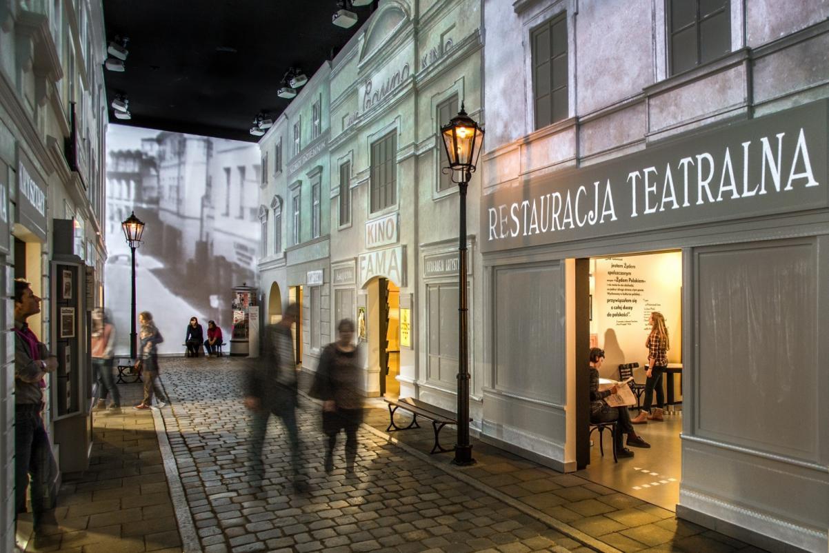 Warsztaty edukacyjne dla szkół ponadpodstawowych. Na zdjęciu: widok ulicy zrekonstruowanej na wystawie muzeum, widać wejścia do kawiarni i kina, środkiem ulicy idzie grupa osób. Światło jest przyciemnione.