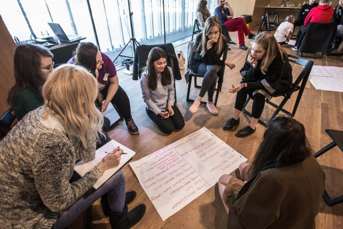 Grupa dziewcząt siedzi w kręgu, pochylają się nad dużym zapisanym arkuszem papieru - warsztaty dla klas 7-8 szkoły podstawowej w muzeum POLIN