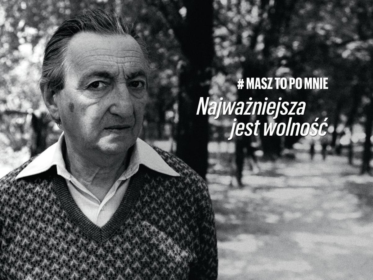 Marek Edelman #MaszToPoMnie - Muzeum POLIN, Na zdjęciu: czarno-biały portret mężczyzny (Marek Edelman, 1989) w koszuli i swetrze, patrzy na nas z profilu, ma poważną minę, w tle piękny park. Obok po prawej biały napis: #MaszToPoMnie