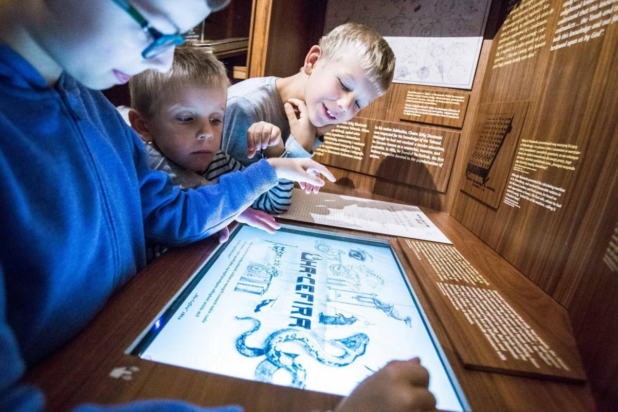 Troje dzieci przed ekranem multimedialnym. Rozwiązują zadanie.