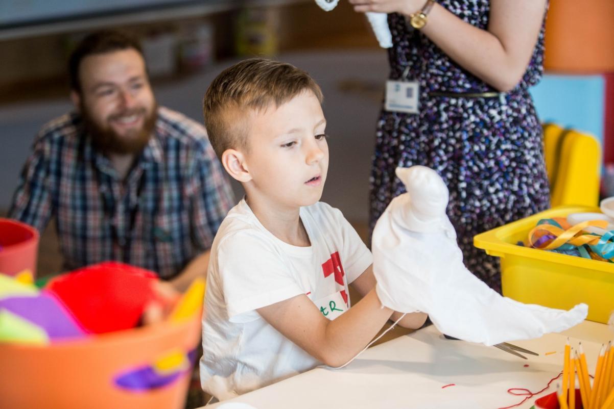 W przy stole, wśród pudeł z kolorowymi przedmiotami, siedzi chłopiec, który trzyma w ręku pacynkę - białego ptaka na patyku