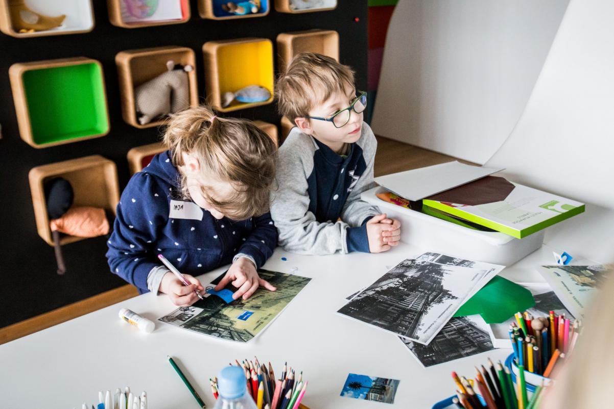 Warsztaty dla szkół w Muzeum POLIN. Na zdjęciu dziewczynka i chłopiec siedzą przy stole nad rozłożonymi starymi zdjęciami i coś do nich doklejają. W tle ściana z kolorowymi półeczkami-boksami.