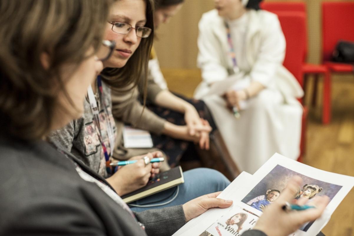 Warsztaty edukacyjne dla szkół ponadpodstawowych. Na zdjęciu trzy kobiety, które dyskutują nad zdjęciami wydrukowanymi na kartkach, które trzyma jedna z nich