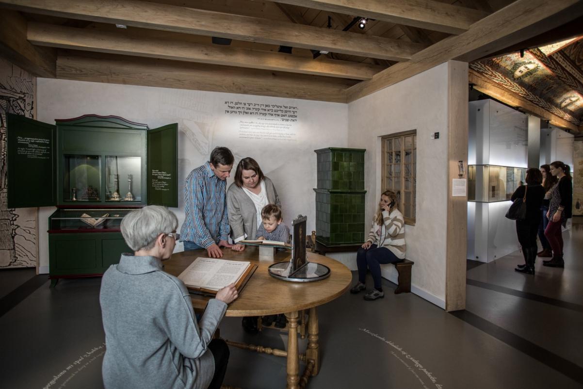 Warsztaty edukacyjne dla szkół ponadpodstawowych. Na zdjęciu przy okrągłym stole, w zainscenizowanej przestrzeni żydowskiego mieszkania, siedzą: kobieta z siwymi włosami, która czyta książkę. Na przeciwko kobieta i mężczyzna oraz dziecko, pochylają się nad inną książką