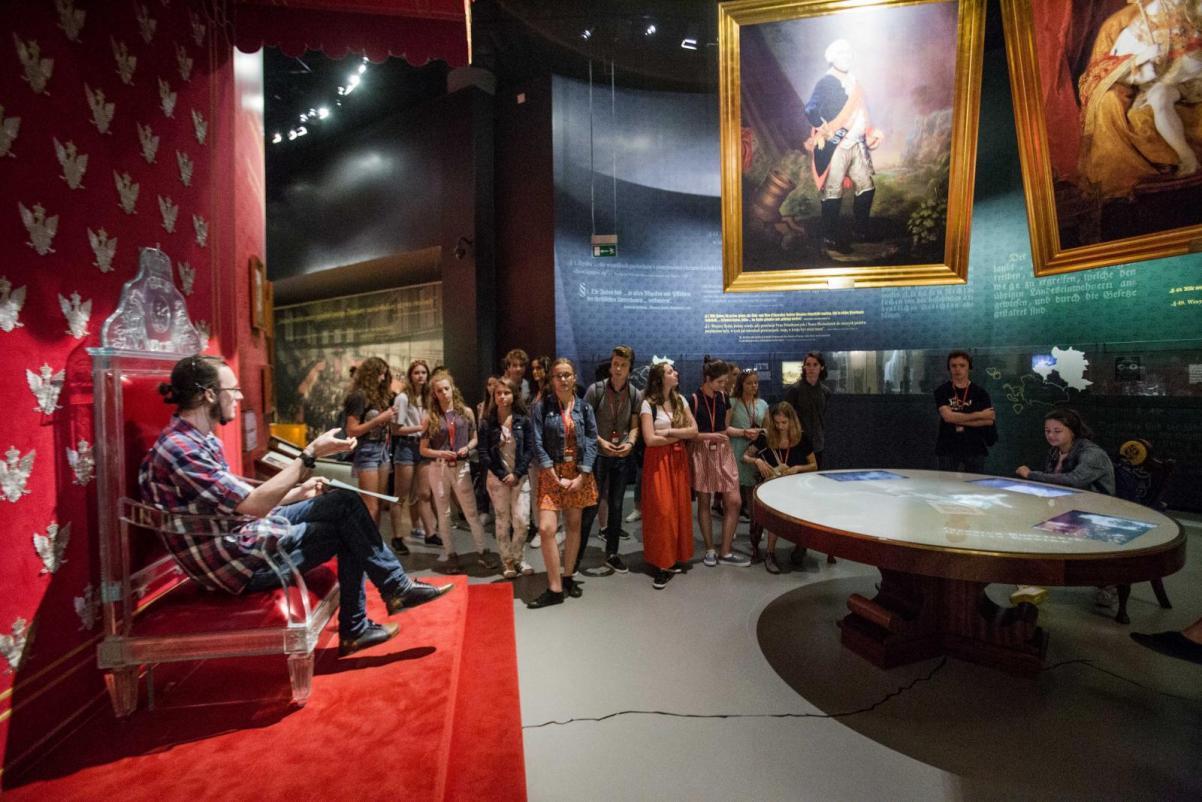 Przewodnicy-Rówieśnicy - III edycja programu. Na zdjęciu: Grupa uczniów w przestrzeni wystawy słucha swojego kolegi, który oprowadza ich po wystawie