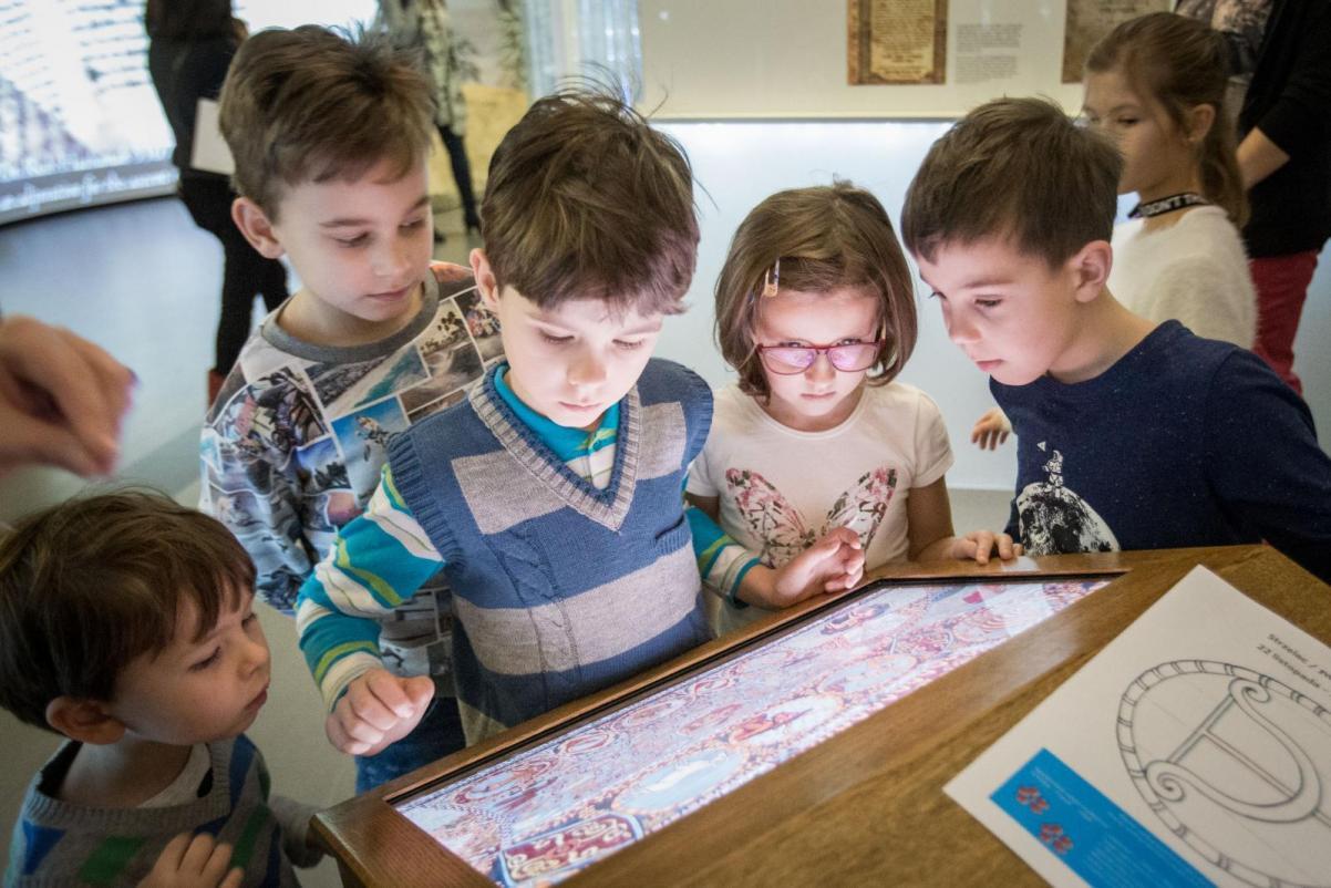 Rosz ha-Szana - spacer z przewodnikiem po wystawie Muzeum POLIN dla rodzin z dziećmi - Opis zdjęcia: grupa chłopców i dziewczynek patrzy w ekran z grą multimedialną. Wszyscy zaciekawieni śledzą wydarzenia na ekranie
