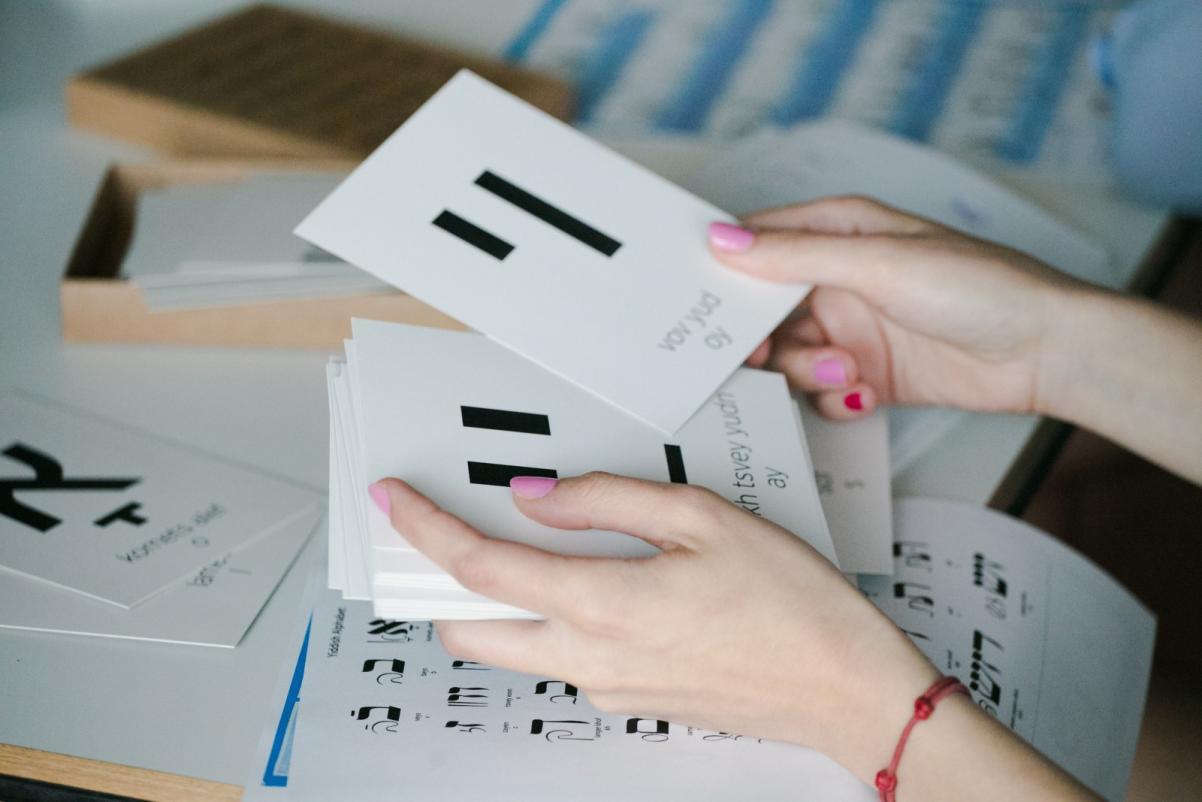 Warsztaty edukacyjne dla szkół ponadpodstawowych. Na zdjęciu widać dłonie, które trzymają duże białe karty z czarnymi hebrajskimi literami - po jednej literze na karcie