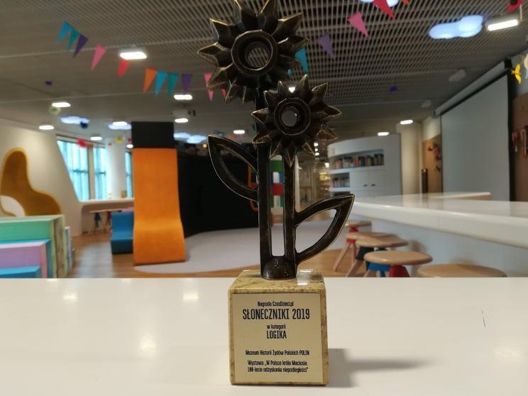 Słoneczniki - Nagroda Złotego Słonecznika dla Muzeum POLIN. Na zdjęciu: na białym stole stoi statuetka Złotego Słonecznika, przedstawiająca dwa kwiaty słonecznika, stojące obok siebie. Statuetka wykonana jest z metalu w kolorze ciemnego brązu.