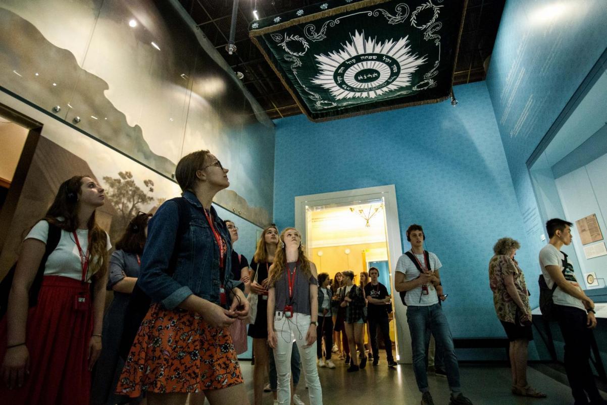 Opis zdjęcia: Grupa młodzieży - dziewczęta i chłopcy - znajduje się w pomieszczeniu wystawy. Ściany są niebieskie, pod sufitem chupa z symbolami żydowskimi. Wszyscy patrzą w prawo na ekspozycję, fot. M. Starowieyska / Muzeum Historii Żydów Polskich