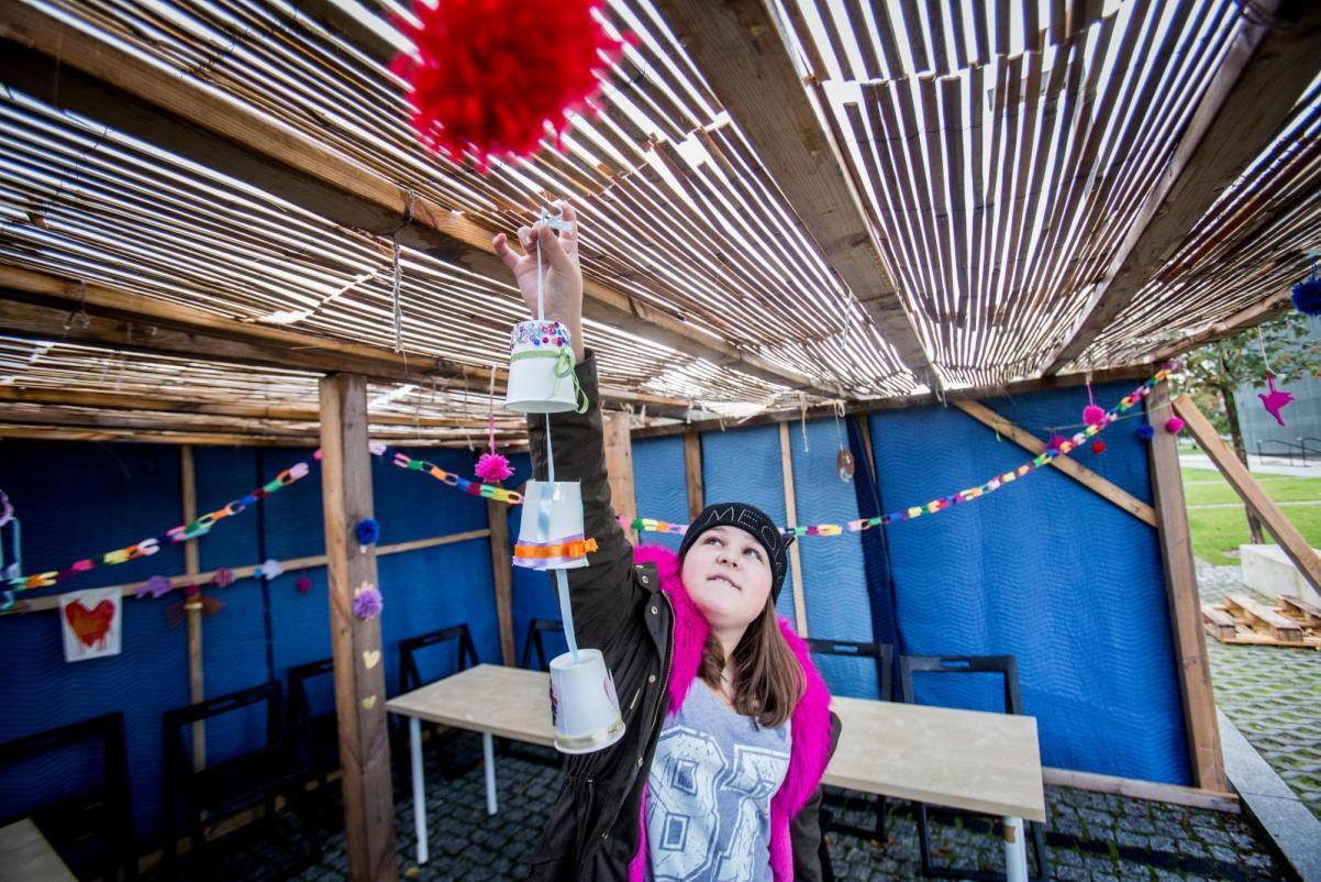 Sukkot - spacer z przewodnikiem po wystawie stałej Muzeum POLIN dla rodzin z dziećmi - Dziewczyna stoi w przygotowanym na Sukkot namiocie - ściany niebieskie, dach z mat trzcinowych. Wiesza pod dachem ozdoby świąteczne, w postaci ozdobionych dzwonków. Ubrana jest w bluzę i czapkę - jesiennie