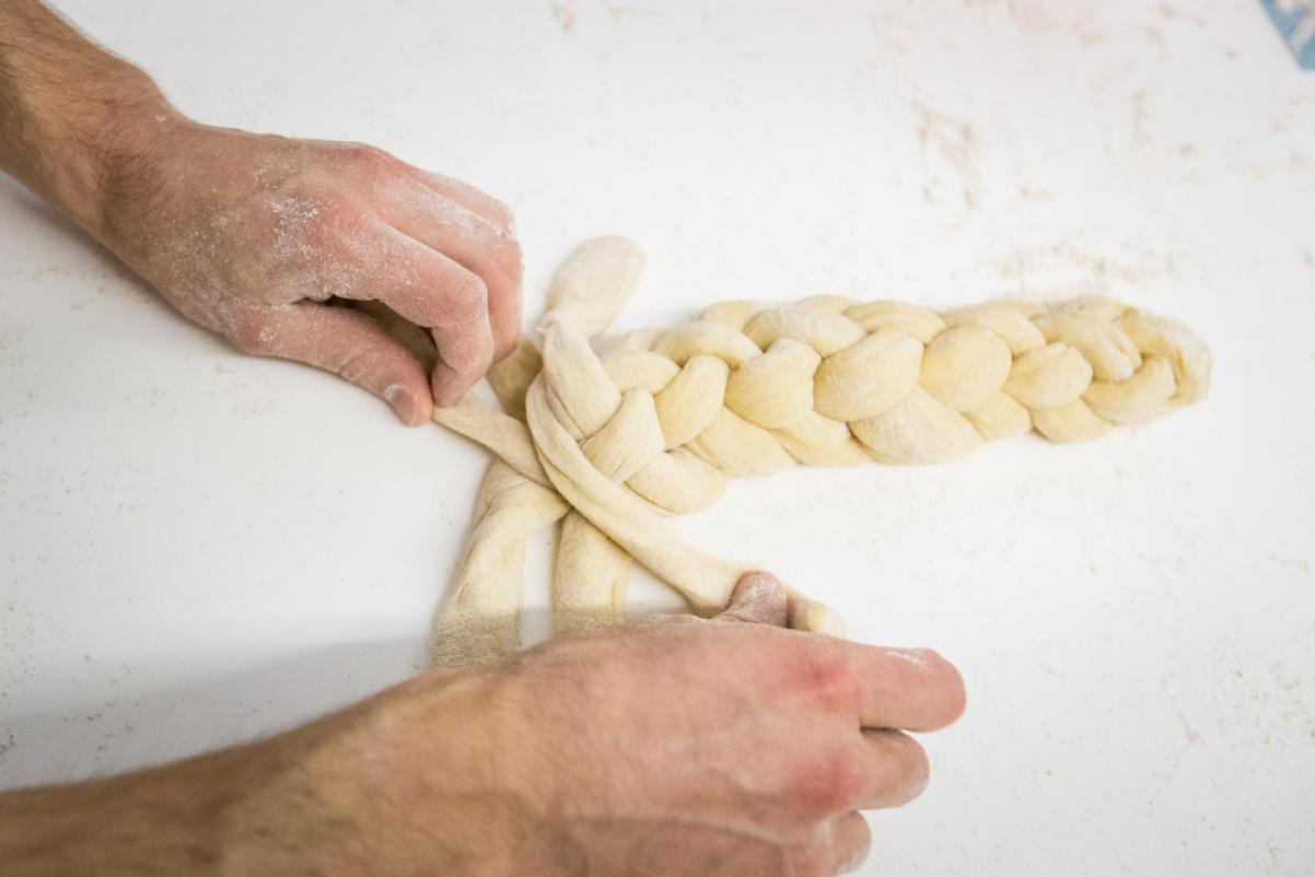 Warsztaty plecenia chałek w Muzeum POLIN w ramach TISZ Festiwalu Żydowskiego Jedzenia. Na zdjęciu widać biały blat, dłonie jednej osoby, które plotą chałkę z czterech pasm ciasta.