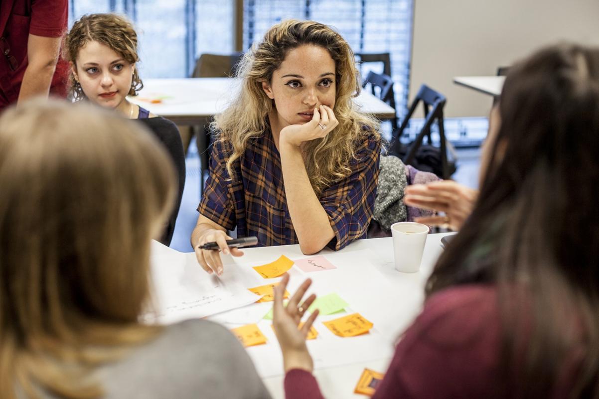 Całodzienne warsztaty antydyskryminacyjne w Muzeum POLIN. Na zdjęciu widać cztery młode kobiety, które siedzą przy stole. Dwie tyłem i dwie przodem do widza. Jedna z kobiet ma przed sobą kartkę z notatkami a w ręku długopis. Słucha kobiety, które siedzą naprzeciwko niej.