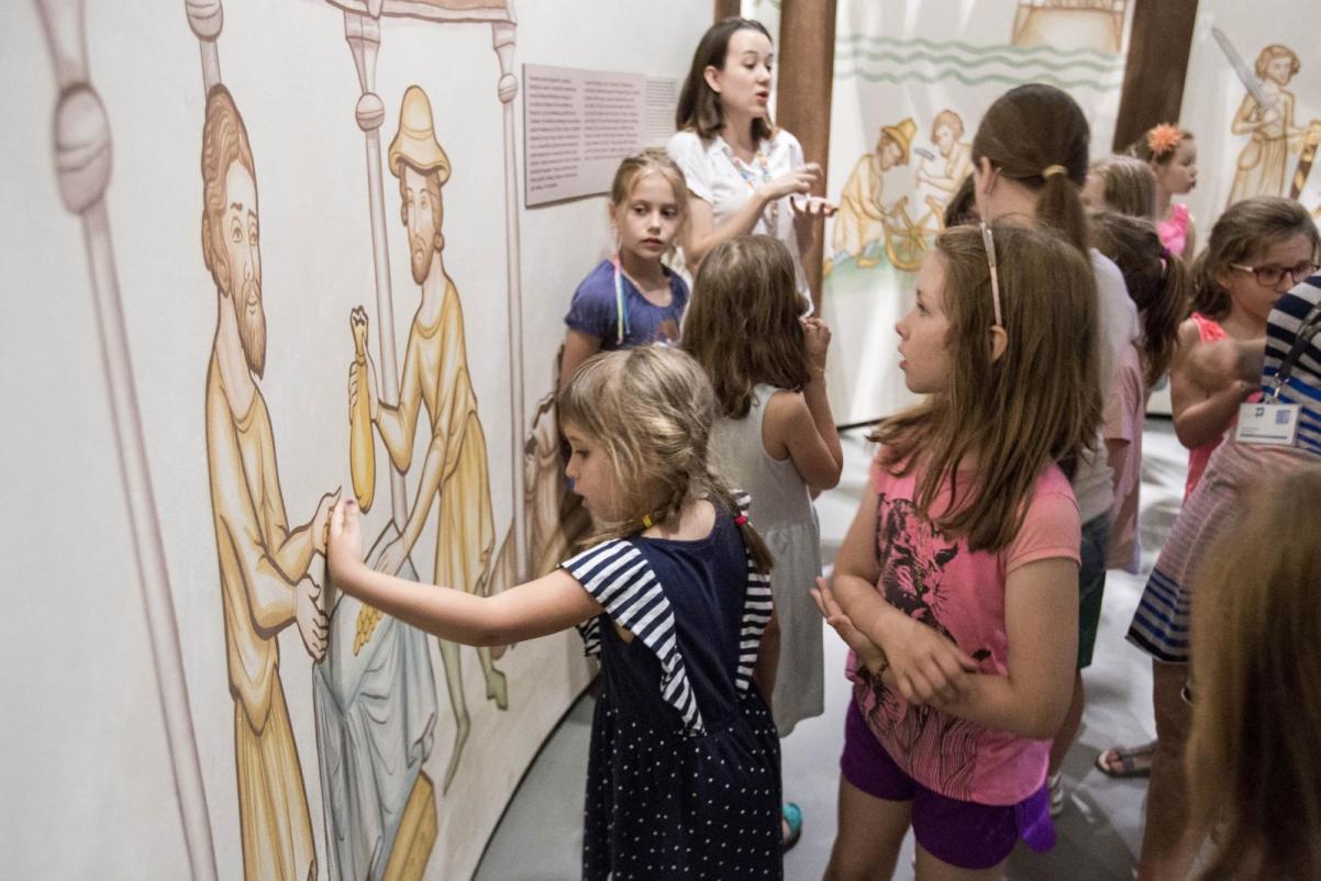 Grupa dzieci (prawa strona zdjęcia) stoi przed rysunkiem na ścianie (lewa strona zdjęcia), przedstawiającym dawnego rzemieślnika. Jedno z dzieci dotyka rysunku. Z tyłu za dziećmi stoi kobieta z ciemnymi włosami do ramion - warsztaty dla szkół podstawowych. klasy 1-3 w Muzeum POLIN